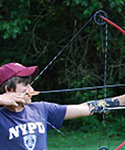 Camper using a bow and arrow at the archery range